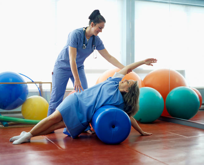 Female doctor helping patient with physiotherapy
